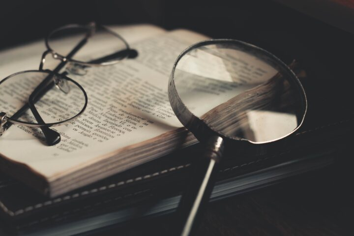magnifying glass and glasses over bible